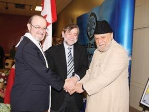 Tiga pembicara pada Konferensi Dunia Agama di Bradford bergandeng tangan. Terry Weller (dari kiri) mewakili Kristen, Mark Freiman mewakili Yahudi dan Mubarak Nazir mewakili Islam. Courtesy PHOTO OF MALIK Khalid Mahmood.